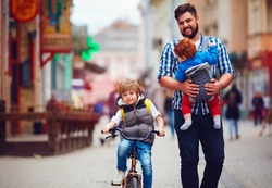happy father and two sons on the city walk. Parental leave. Baby carrier
