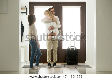 Happy father arrived home returning after business trip with baggage, daddy missed little daughter holding in arms hugging girl while wife standing in hall, family reunion, welcome back dad concept  #744304771