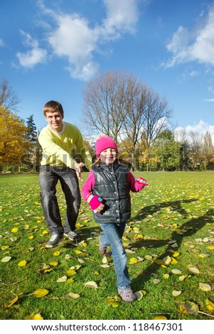Happy father chasing his  little daughter in autumn park - stock photo