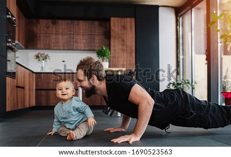 Happy father doing push ups next to his infant baby at home. Looking at his baby, moved and amused by him. Family quarantine, domestic life in self-isolation. Sunset light from the windows