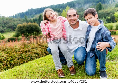 Happy father enjoying with his kids outdoors and smiling