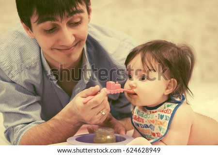 Happy father feeding baby girl at home