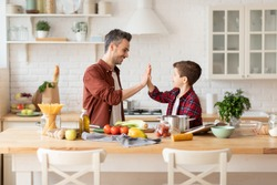 Happy father give high five to loving son on home kitchen. Dad and child being team while cooking. Positive parent and kid nice relationship. Happy family pastime, communication and support