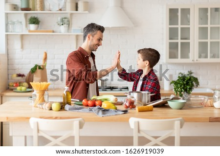 Happy father give high five to loving son on home kitchen. Dad and child being team while cooking. Positive parent and kid nice relationship. Happy family pastime, communication and support Foto stock ©