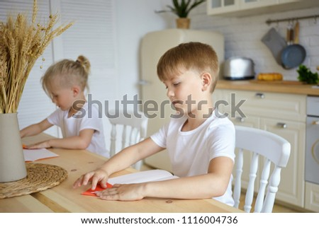 Happy father helping hiHandsome serious schoolboy and his little blonde brother sitting at wooden table and doing homework. Two brothers siblings reading at kitchen counter. Family, childhood concept stock photo