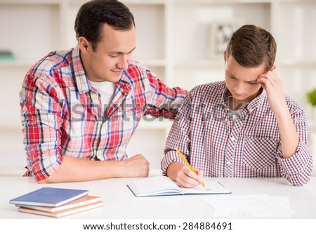 Happy father helping his son to do homework.