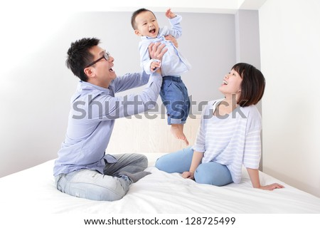 happy father hug his son with smile mother sitting on bed at home, asian family