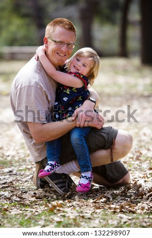 Happy father hugging his adorable toddler daughter