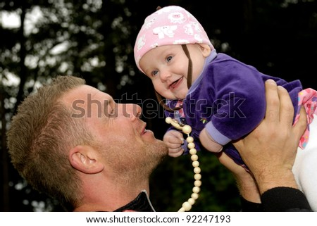 Happy father is lifting up his smiling baby
