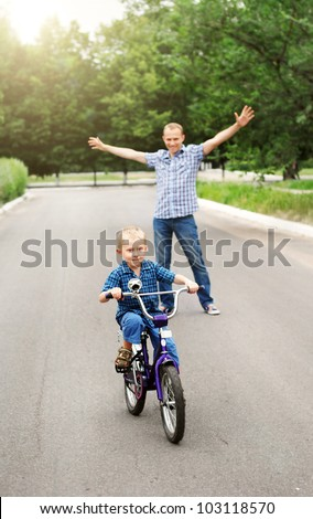 Happy father is train his son to ride a bicycle