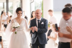 Happy father leading his daughter to the altar. Dad is proud of his beautiful daughter. Wedding ceremony