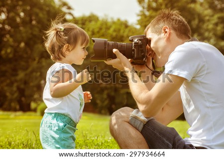 Happy father making photo of his daughter using professional camera