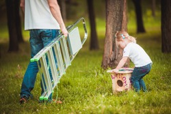 Happy father making Wooden birdhouse with daughter in summer green park