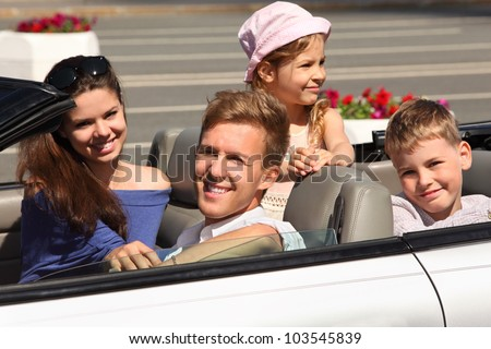 Happy father, mother and two children ride in convertible car; focus on man