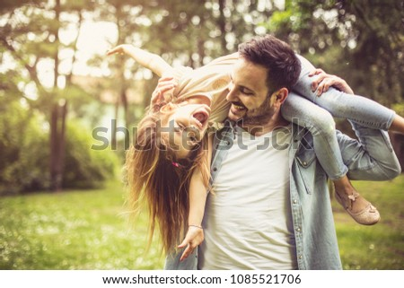 Happy father playing and carrying his daughter on shoulders. - Shutterstock ID 1085521706