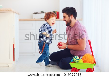 happy father playing with cute toddler baby son at home, family games