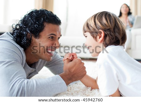 Happy father playing with his son in the living-room