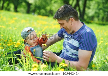 Happy father playing with little child son boy in spring park outdoors