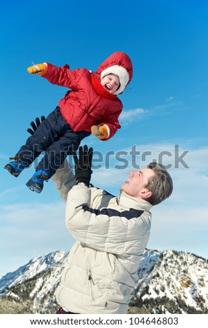 Happy father playing with little child son boy in winter over mountain and blue sky