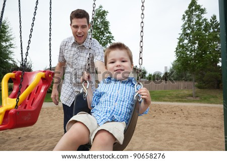 Happy father pushing boy on swing in playground