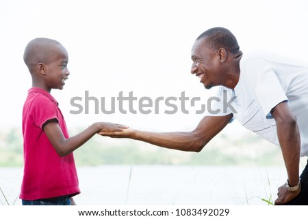 Happy father reaches out to his son outside. He wishes to drive his son outdoors in confidence and protection. the parental concept of parental care. road to life. #1083492029