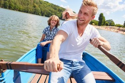 Happy father rowing his family in a boat on a lake on summer vacation