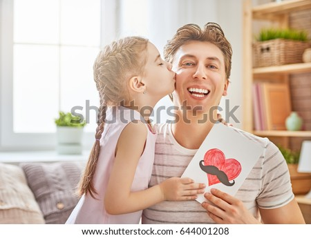 Happy father's day! Child daughter congratulates dad and gives him postcard. Daddy and girl, kissing, smiling and hugging. Family holiday and togetherness. #644001208