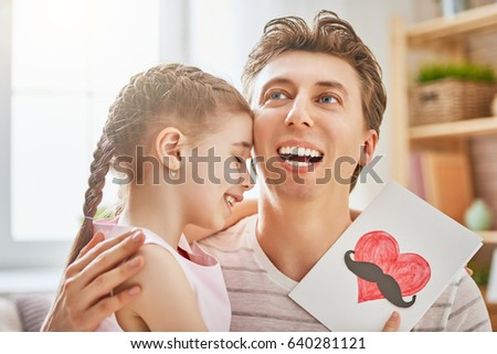 Happy father's day! Child daughter congratulates dad and gives him postcard. Daddy and girl smiling and hugging. Family holiday and togetherness. #640281121
