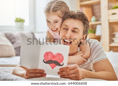 Happy father's day! Child daughter congratulates dad and gives him postcard. Daddy and girl smiling and hugging. Family holiday and togetherness. #644006608