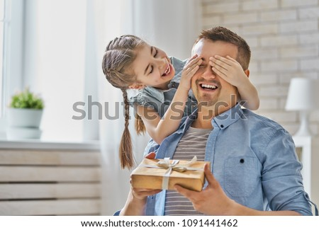 Happy father's day! Child daughter congratulating dad and giving him gift box. Daddy and girl smiling and hugging. Family holiday and togetherness.
