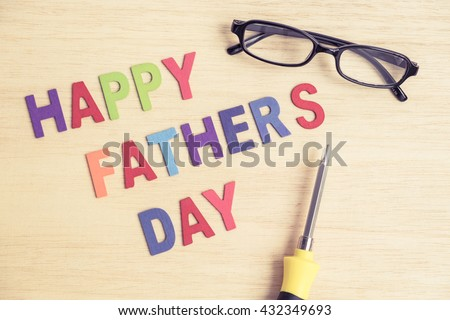 Happy Father's Day - colorful wording on wood background with black glasses and screwdriver - vintage tone filter #432349693