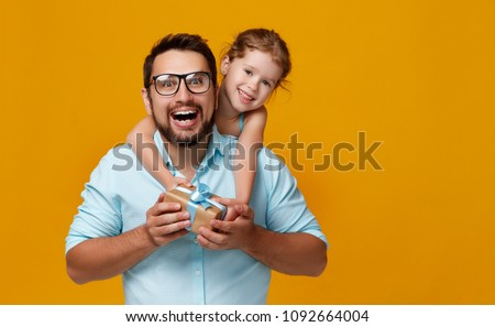 happy father's day! cute dad and daughter hugging on colored yellow background\r