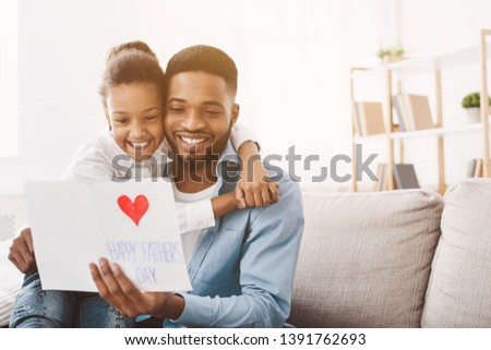 Happy father's day. Daughter congratulating dad and giving him postcard, free space