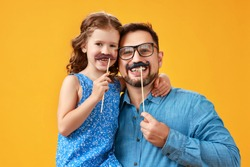 happy father's day! funny dad and daughter with mustache fooling around on colored yellow background