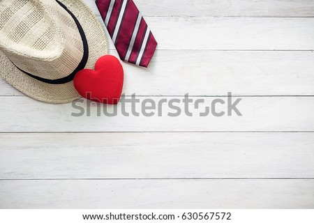 Happy Father's Day inscription with colorful tie,red heart and hat on wooden background floor backround.