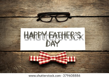 Happy Father\'s Day inscription with red bow tie and glasses on wooden background. Greetings and presents