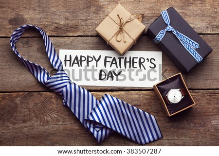 Happy Father\'s Day inscription with tie and watch on wooden background. Greetings and presents