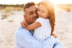 Happy father spending fun time with his little daughter at the beach, hugging