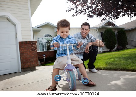 Happy father teaching his adorable son to ride a tricycle