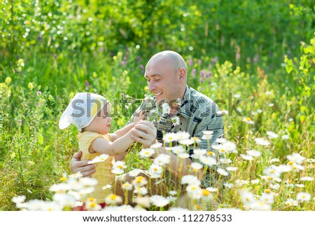 Happy father with daughter in summer daisy plant