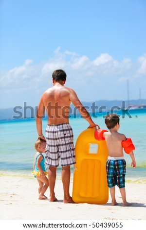 Happy father with his two kids enjoying beach vacation