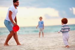 happy father with kids, family playing flying disc golf on evening beach