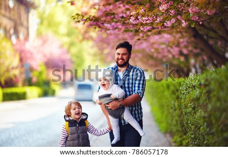 happy father with kids on the walk in spring city, baby carrier, paternal leave