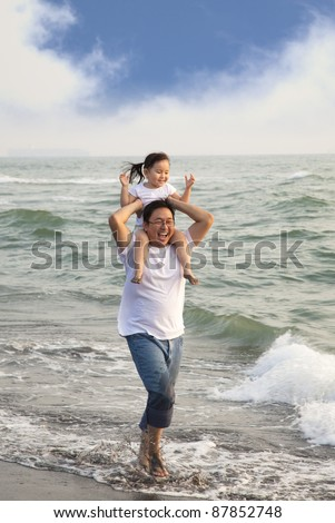 happy father with little girl walking on the beach - stock photo