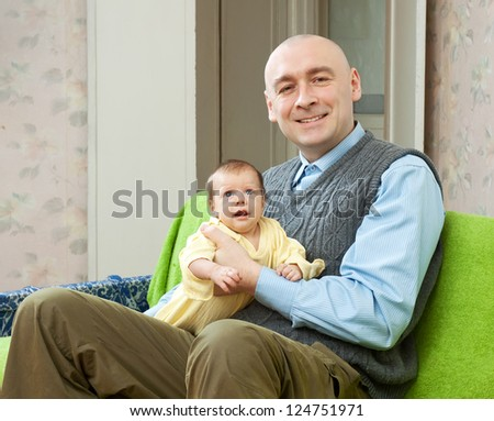 Happy father with  2 month child in home interior