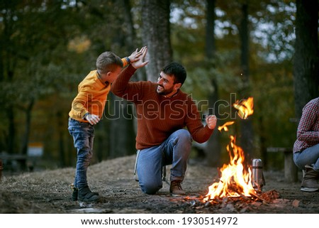 Happy father with son giving five near campfire