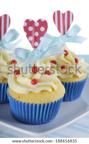 Happy Fathers Day bright and cheery red white and blue decorated cupcakes with heart toppers and gift tag on vintage blue shabby chic background.