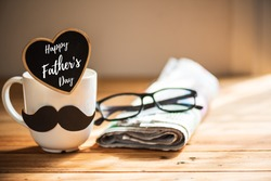 Happy fathers day concept. coffee cup with black paper mustache, heart tag with  Happy father's day text and newspaper, glasses on wooden table background.