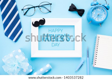 Happy fathers day concept. Top view of blue tie, beautiful gift box, alarm clock, white picture frame with Happy father's day text and retro film camera on bright blue pastel background. Flat lay.