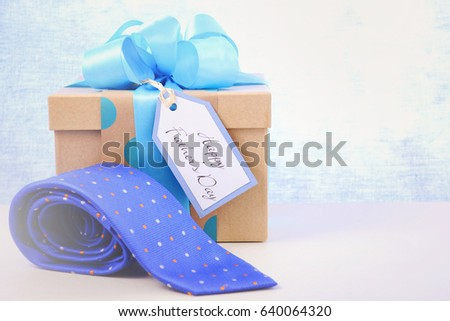 Happy Fathers Day gift and neck tie on white wood table and pale blue background, with applied retro style filters.